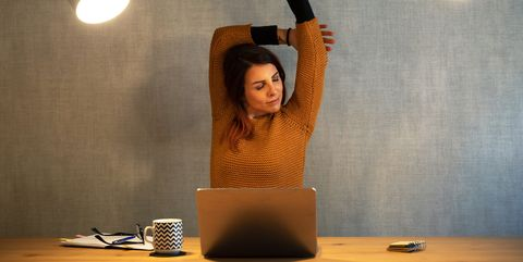 young woman working at home with laptop arms stretched