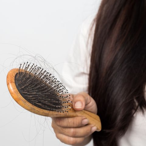 young woman worried about hair loss on a white