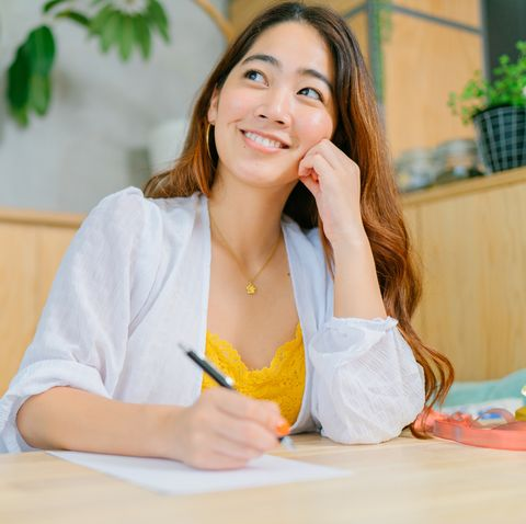 young woman writing letter to put inside gift box in living room at home
