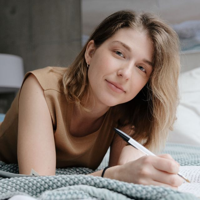 young woman writing on bed