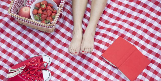 young woman's feet on a checkered blanket with a picnic basket, shoes, and a book