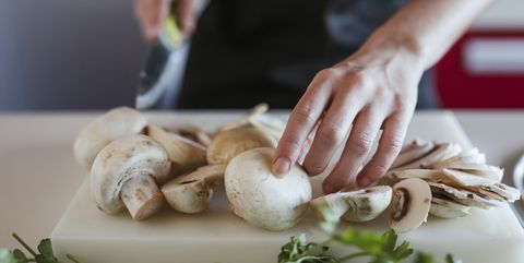 young woman's hands preparing champignons, closeup