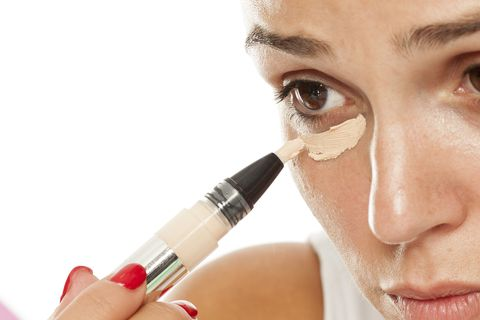 young women applied concealer under the eyes with applicator