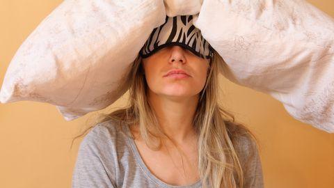 jonge vrouw met slaapmasker en kussen op het hoofd