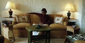Yves Saint Laurent is reading a book on a sofa