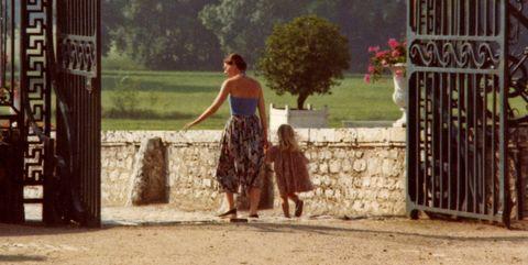 moeder met dochter, hand in hand, die door een hek lopen