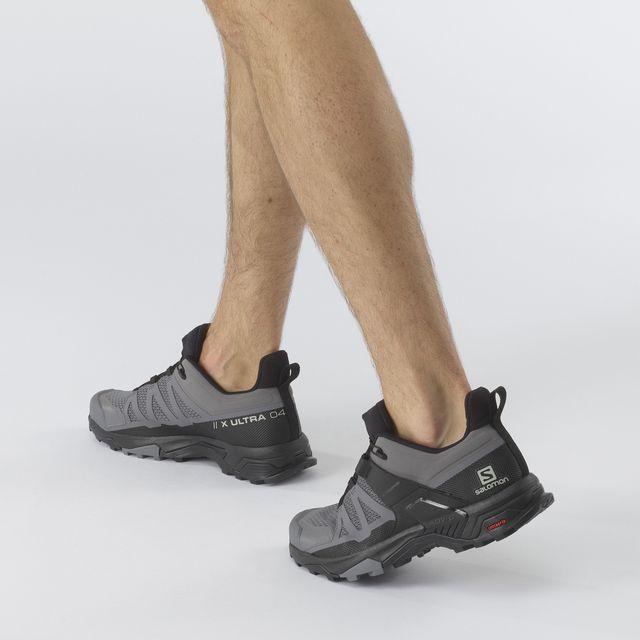piernas de un hombre con las salomon x ultra 4, zapatilla de senderismo en color gris