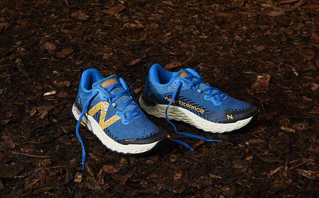 la zapatilla de trail running new balance fresh foam hierro v6 en color azul y amarillo en un terreno lleno de hojas