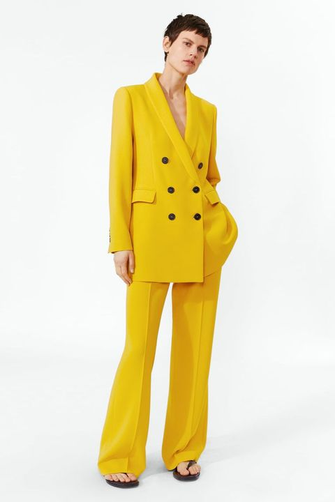 Clothing, Suit, Yellow, Formal wear, Pantsuit, Standing, Outerwear, Blazer, Button, Tuxedo,