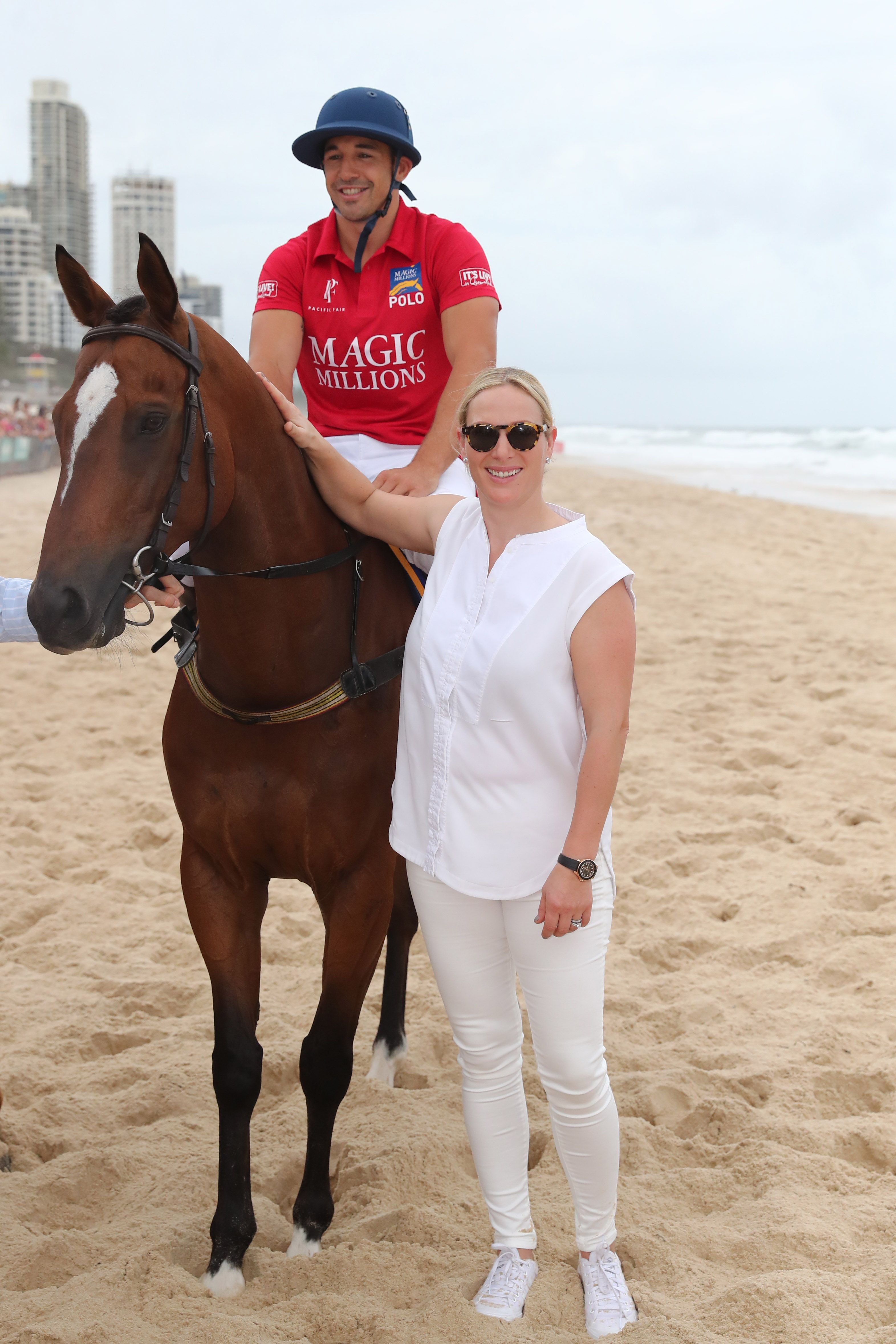 Zara Tindall wore a casual white button down, white jeans, sneakers, and tortoise shell sunglasses as she posed with equestrian Billy Slater during the 2019 Magic Millions draw.