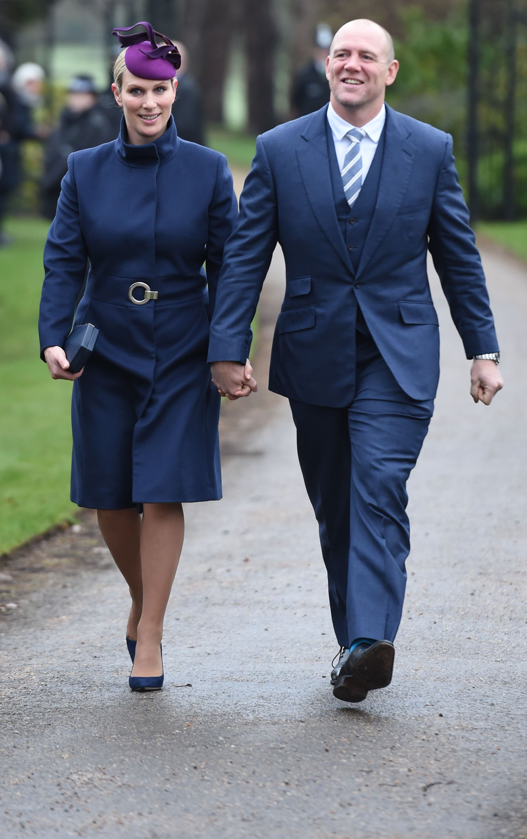 Zara Tindall paired a belted coat dress with a violet fascinator and a navy clutch and pumps to attend the Christmas Day church service on the Sandringham estate.