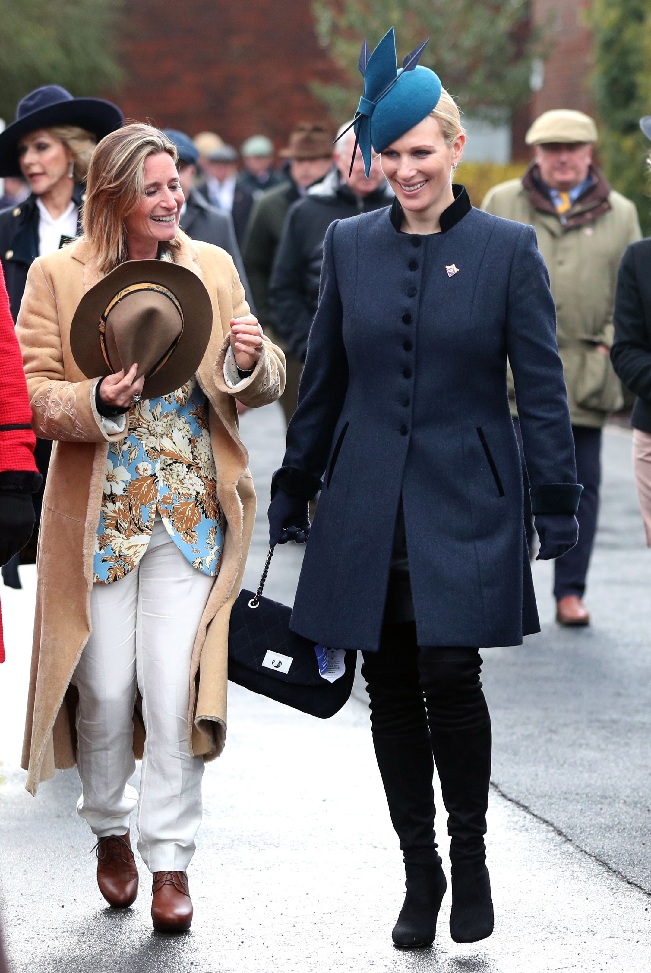 Zara Tindall bundled up in a navy high-collared tweed coat for a day at Cheltenham Festival's races. The young royal topped her outfit off with a cerulean cocktail hat, Stuart Weitzman boots and a quilted black handbag.