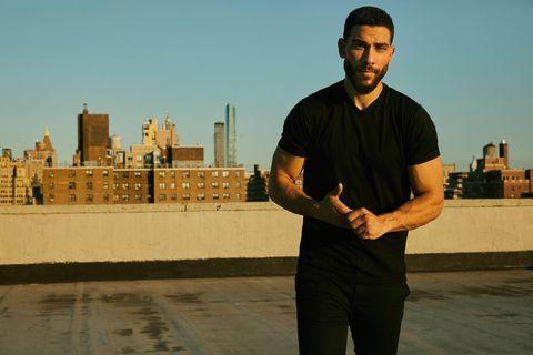 Sleeve, Standing, Elbow, Facial hair, Roof, Beard, Tower block, Pocket, Skyline, Tower,