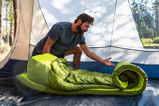 a man unrolling a green sleeping bag and camping mattress
