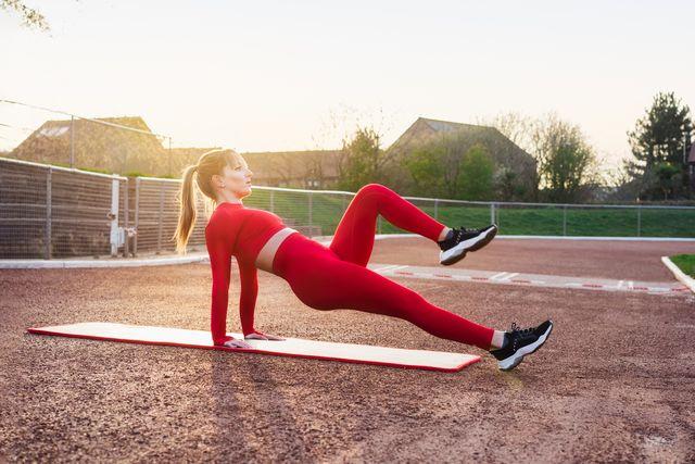 vrouw doet omgekeerde plank op atletiekbaan bij ondergaande zon