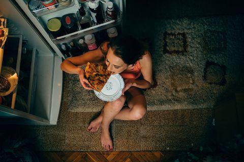 Vrouw eet 's nachts een pizza voor de koelkast