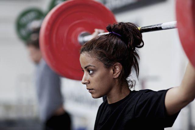 vrouw tilt barbell met gewicht boven haar hoofd in sportschool