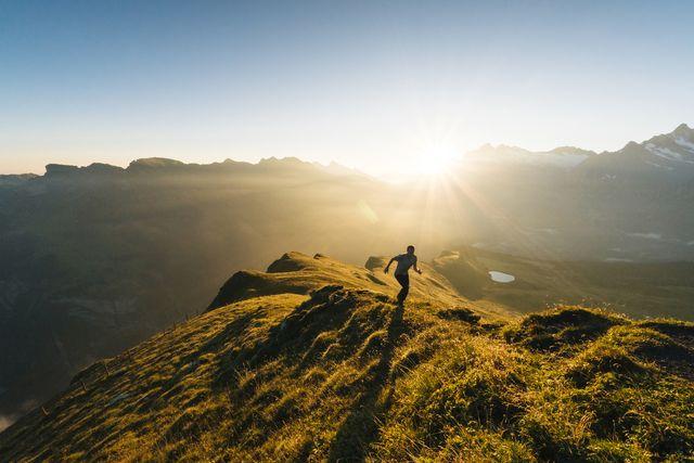 man aan het hardlopen over bergkam bij ondergaande zon