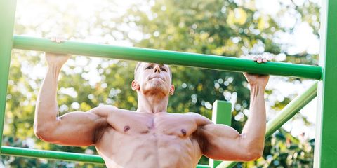 Young male muscular athlete exercises pull ups outdoors in summer
