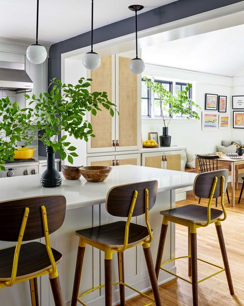 kitchen with light olive cabinets, dark brown and yellow bar stools