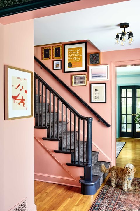pink painted entryway with black staircase banister and dark gray checkered stair runner, gallery wall