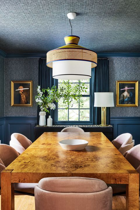 brown dining table, pink velvet cushioned dining chairs, blue painted walls with dark blue wall covering, wall art in gold frames