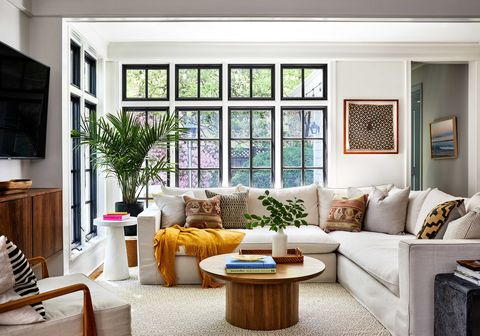 living room with gray sectional sofa, circular wooden coffee table, wall mounted tv, yellow throw rug and decorative cushions