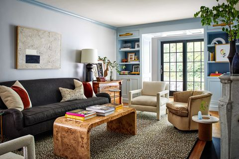 sitting room with black sofa, wooden coffee table with coffee table books, light blue painted walls