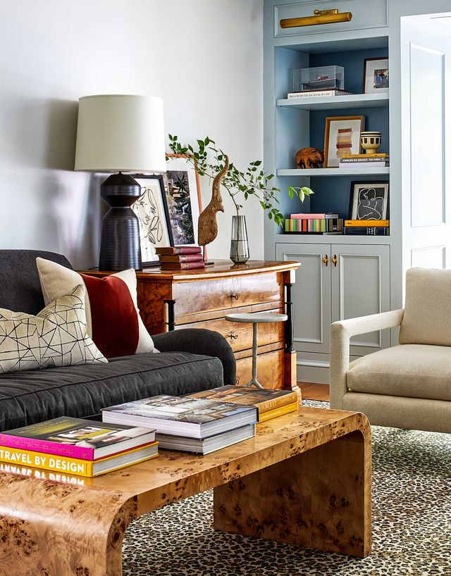 living room, dark gray sofa with wooden coffee table and coffee table books, wooden console, artwork and decorative sculpture