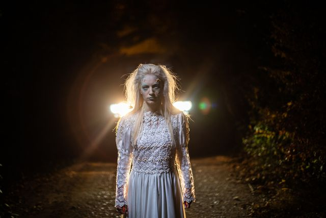 zombie in wedding dress standing on a road at night