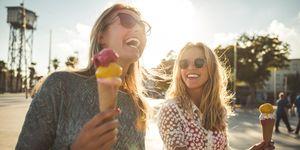 Vrouwen eten lachend een ijsje in de zon