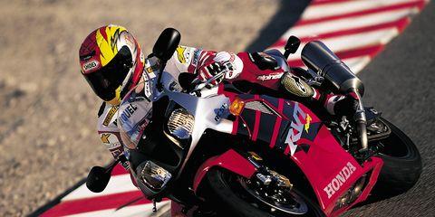 Motorcycle, Motorcycle helmet, Motorsport, Sports gear, Personal protective equipment, Helmet, Race track, Motorcycle racing, Automotive tire, Motorcycling,