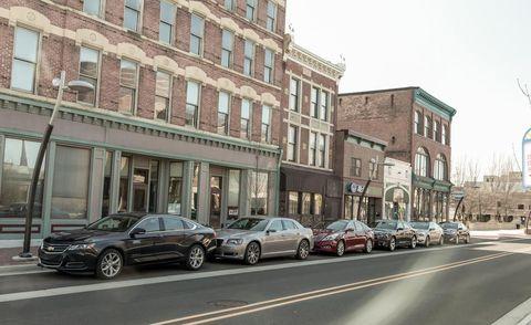 Window, Automotive parking light, Land vehicle, Neighbourhood, Car, Town, Facade, Full-size car, Automotive lighting, Mixed-use,