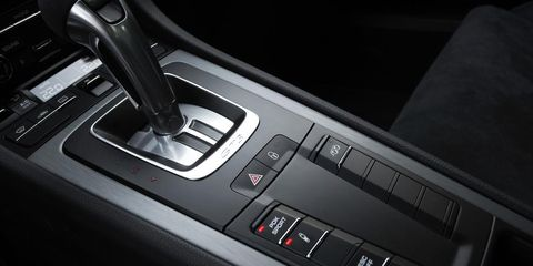 Automotive design, Personal luxury car, Luxury vehicle, Center console, Gear shift, Steering part, Steering wheel, Machine, Carbon, Sports car,