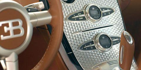Motor vehicle, Automotive design, Steering wheel, Steering part, Logo, Metal, Gear shift, Luxury vehicle, Machine, Circle,