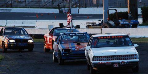 Land vehicle, Vehicle, Car, Automotive parking light, Automotive exterior, Motorsport, Flag, Classic car, Bumper, Sedan,