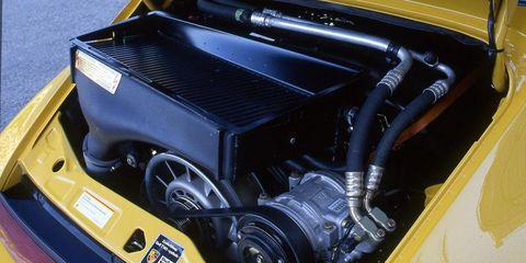 Motor vehicle, Automotive design, Yellow, Automotive exterior, Machine, Engine, Automotive lighting, Bumper, Automotive light bulb, Auto part,