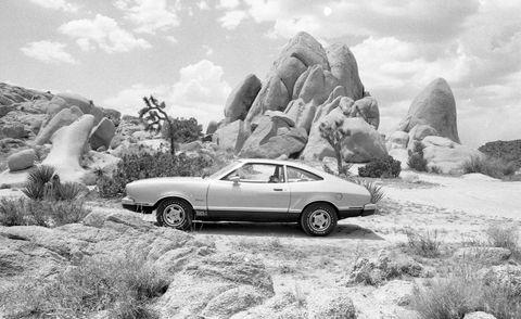 Tire, Land vehicle, Automotive design, Car, Rock, Classic car, Bedrock, Alloy wheel, Boulder, Outcrop,