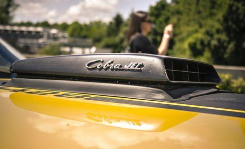Motor vehicle, Mode of transport, Automotive design, Yellow, Automotive exterior, Hood, Logo, Windshield, Automotive decal, Windscreen wiper,