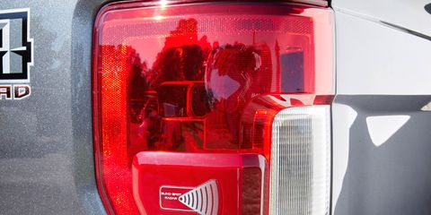 Motor vehicle, Automotive tail & brake light, Automotive lighting, Automotive exterior, Automotive design, Red, Automotive parking light, Fender, Light, Logo,