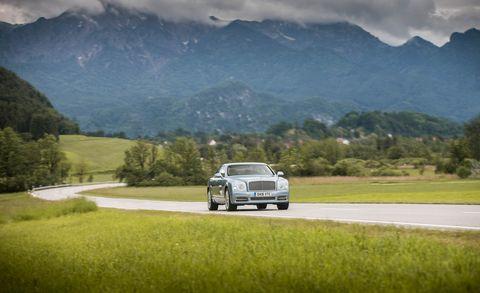 Motor vehicle, Road, Automotive design, Mountainous landforms, Automotive parking light, Mountain range, Highland, Natural landscape, Landscape, Plain,
