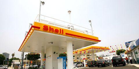 Land vehicle, Automotive parking light, Automotive lighting, Filling station, Asphalt, Gas pump, Fuel, Advertising, Family car, Gasoline,