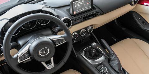 Land vehicle, Vehicle, Car, Center console, Mazda, Steering wheel, Mazda mx-5, Automotive design, Personal luxury car, Font,