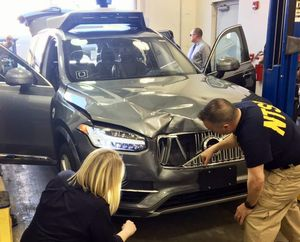 Investigators from the National Transportation Safety Board examine the Volvo XC90 which struck a pedestrian in Tempe, Arizona, on Sunday night.