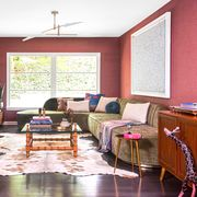 living room, red wall covering, green sofa, wooden bar cabinet