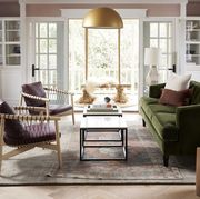 living room, green couch, gold semi circle chandelier, double coffee tables