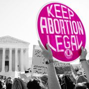 """a woman holding up a sign that says """"keep abortion legal"""""""