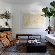 living room, white couch, leather lounge chairs, rug, wall art, fiddle leaf fig