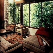 room with glass walls and wood beams and rustic pattern rug and pillows