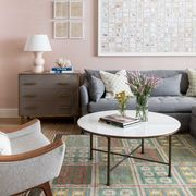 pink wallpaper, gray sofa, circular coffee table, wall art